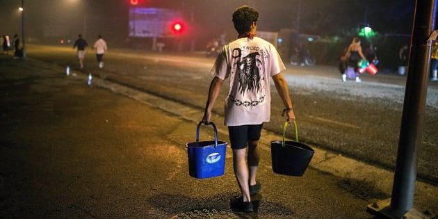 Un hombre porta dos cubos de agua para ayudar a sofocar uno de los focos declarados en el centro de la ciudad de Vigo.