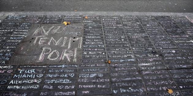 Un taxi pasa junto a los mensajes de apoyo escritos con tiza en una acera de Las Ramblas de Barcelona.