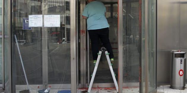 Un operario limpia las pintadas que un grupo de desconocidos ha realizado hoy en la sede de la Agencia Vasca del Turismo (Basquetour) en Bilbao.