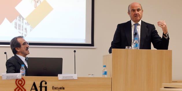 El ministro de Economía, Luis De Guindos, bajo la atenta mirada del presidente de Analistas Financieros Internacionales, Emilio Ontiveros, en la sede de AFI. EFE/Álvaro Sánchez