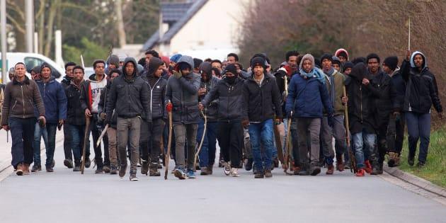 Un grupo de inmigrantes carga palos y piedras durante un enfrentamiento cerca del puerto de Calais.
