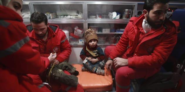 Personal de la Media Luna Roja y un niño durante la evacuación.