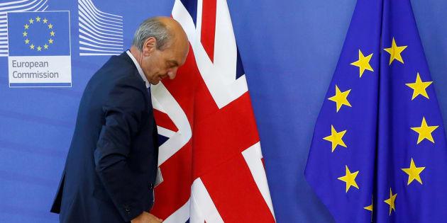 Un trabajador pasa junto a las banderas de Reino Unido y la UE en Bruselas.