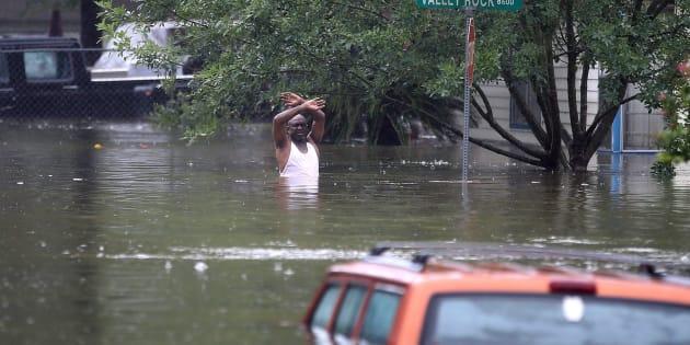 Un hombre hundido hasta la cintura en agua sucia gesticula hacia el equipo de rescarte que se aproxima en Houston.