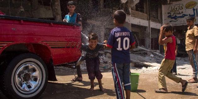 Niños juegan junto a un vehículo en Mosul, liberado del Estado Islámico.