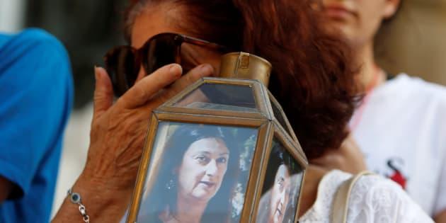 Una mujer sujeta la foto de la periodista asesinada.