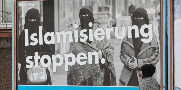 Una mujer pasa junto a un cartel electoral de AfD contra la inmigración en Alemania.