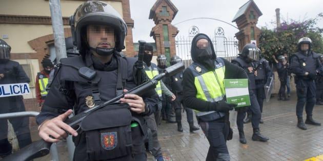 Agentes antidisturbios de la Policía Nacional retiran material electoral de un instituto de L'Hospitalet de Llobregat.
