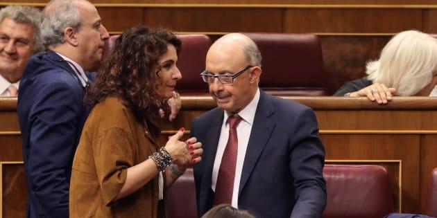 La ministra de Hacienda, María Jesús Montero, conversa con el exministro Cristóbal Montoro en el Congreso.