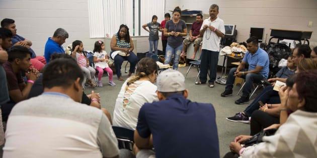 Un grupo de gente forma un círculo para rezar en una clase del colegio Pizzo Elementary de Tampa, un refugio temporal ante el huracán Irma.
