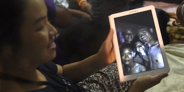 A happy family member shows the latest pictures of the missing boys taken by rescue divers inside Tham Luang cave  on July 2, 2018.