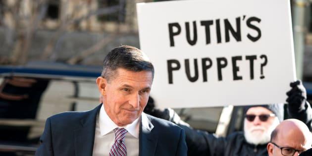 Flynn a su llegada al Tribunal Federal ante un manifestante (c) con una pancarta que reza: ''¿La marioneta de Putin?''
