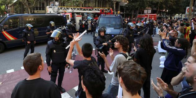 Policías y manifestantes en la puerta de la sede de la CUP