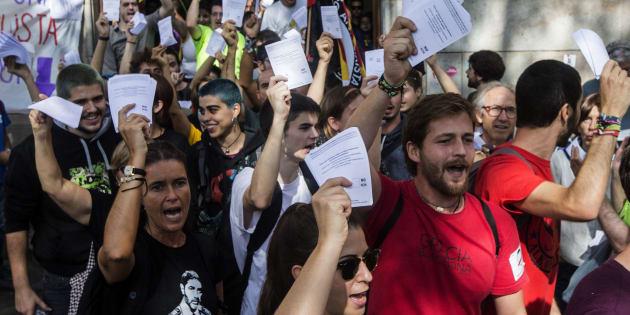 Varios estudiantes salen de la Universidad de Barcelona con papeletas del referéndum independentista.