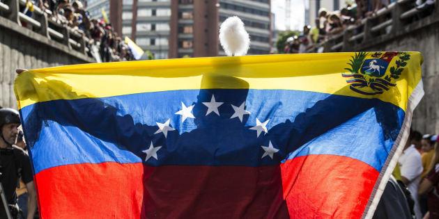 Una persona extiende una bandera venezolana ante decenas de manifestantes antigubernamentales.
