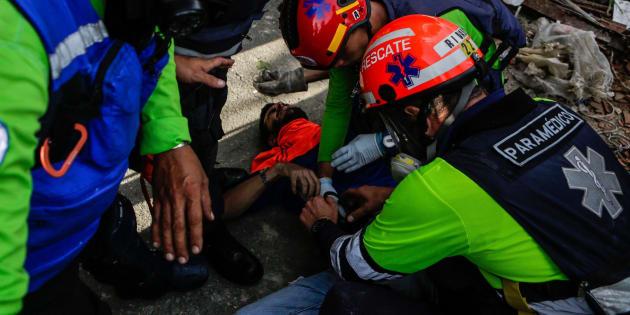 Personal médico auxilia a un manifestante herido durante las manifestaciones del lunes en Venezuela.