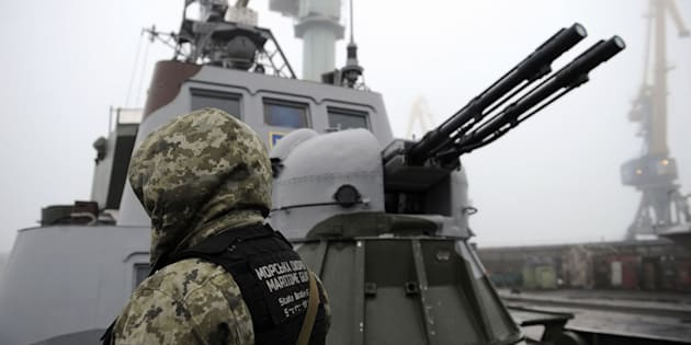 Un soldado ucraniano junto a un buque en el mar de Azov.
