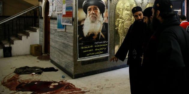 Varios religiosos coptos observan los rastros de sangre en el lugar del ataque.