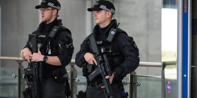 Dos policías armados patrullan los alrededores del lugar del ataque.