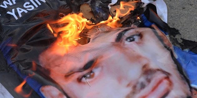 A poster of Yasin Bhatkal, an alleged founder of the Indian Mujahideen, burns after being set on fire by demonstrators celebrating his arrest in Bangalore on August 29, 2013.