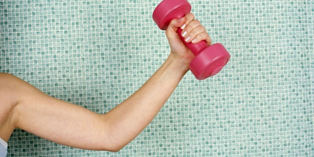 Young woman lifting dumbbell, against tiled wall, close-up
