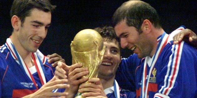 Bixente Lizarazu y Zinedine Zidane sostienen la copa, observados por Robert Pires luego de que su equipo derrotara a Brasil durante la final del Mundial de Francia de 1998 en el Stade de France en París, el 12 de julio.