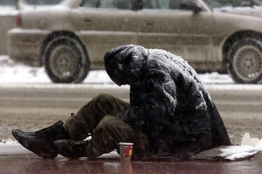 Un hombre pidiendo limosna bajo una nevada en Toronto, Canadá.