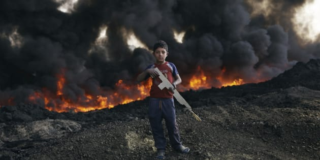 Zaer Ibrahim*, 8 plays by the burning oil fields in Qayyarah.   *Name changed to protect identity