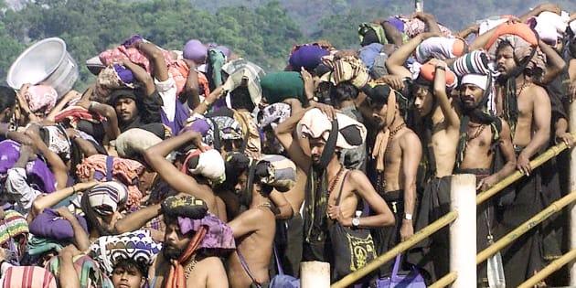 "Hindu pilgrims queue outside the Sabarimala Temple to offer prayers to the Hindu deity ""Ayappa"" in Kerala, on January 15, 2003."