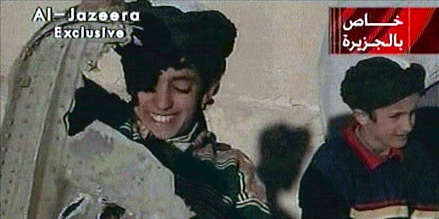 Picture taken from undated Al Jazeera television footage purportedly shows Hamza bin Osama bin Laden (L), one of the sons of Saudi-born dissident Osama bin Laden, displaying what the Taliban say is wreckage from a U.S. helicopter near Ghazni. Child at right is unidentified. [ U.S. B-52  bombers continued to pound the front line of Taliban forces north of the Afghan capital November 7, 2001.    ]  POOR QUALITY VIDEO DOCUMENT (CREDIT REUTERS/Al-Jazeera TV)