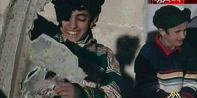 Picture taken from undated Al Jazeera television footage purportedly shows Hamza bin Osama bin Laden (L) displaying what the Taliban say is wreckage from a U.S. helicopter near Ghazni.