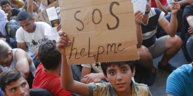 Un niño refugiado pide ayuda con un cartel de cartón, mientras espera en las vías de la estación de Budapest (Hungría) a que le permitan continuar camino hacia Alemania.