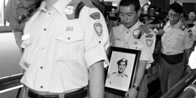殉職した高田晴行警視の遺影を胸にカンボジアから帰国した文民警察官(千葉・成田空港) 撮影日:1993年07月08日