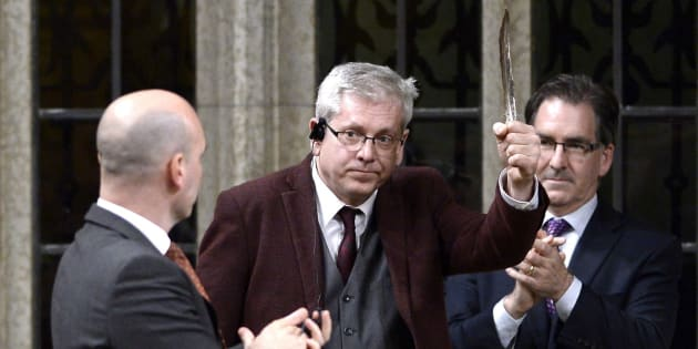 NDP MP Charlie Angus holds a feather as he rises to vote in favour of the NDP's motion calling on the House of Commons to officially ask the Pope to apologize to residential school survivors on Parliament Hill on May 1, 2018.