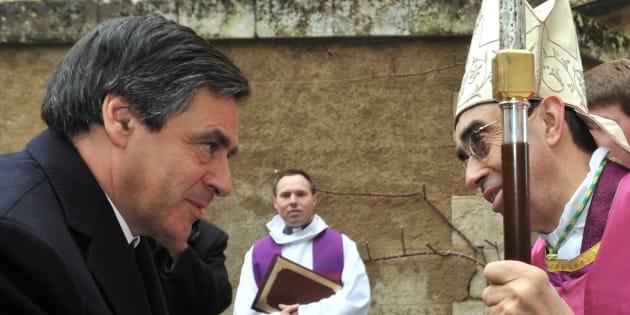 Francois Fillon salue l'évêque Alain Castet lors d'une messe en hommage aux victimes de la tempête Xynthia, le 4 mars 2010.  REUTERS/Franck Perry/Pool