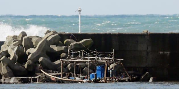 国籍不明の男性8人が乗って来たとみられる木造船(中央)=24日、秋田県由利本荘市