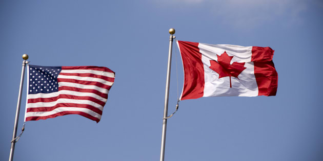 File photo of American and Canadian flags flying side by side.
