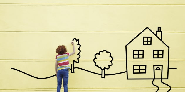 Girl drawing a house and trees onto a wall