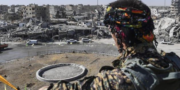 Un membre des Forces démocratiques syriennes contemple les ruines de Raqa.