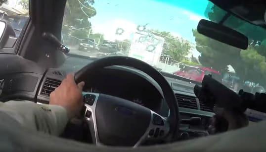 En pleine poursuite, ce policier lâche le volant et tire à travers son