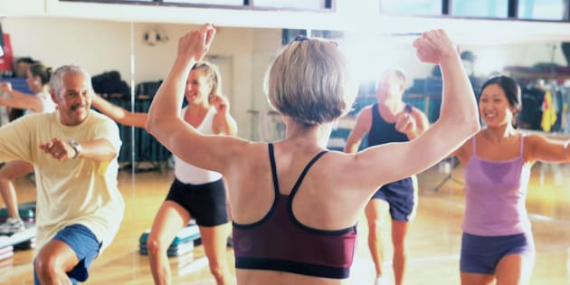 Rear view of a female aerobics instructor giving instruction in a step aerobics class
