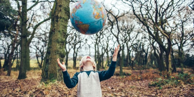 Little boy outdoors in the woods throwing a globe up in the air