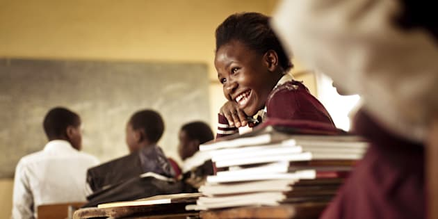 A Happy young South African girl (from the Xhosa tribe) works on her studies and jokes with her friends at at an old worn desk in a class room in the Transkei region of rural South Africa.