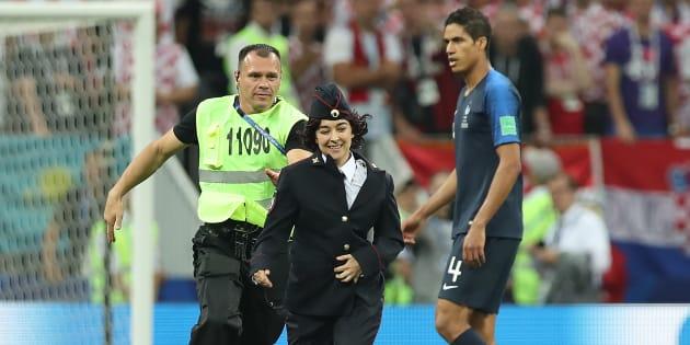 サッカー・ワールドカップの決勝戦に警察官姿で乱入したプッシー・ライオットのメンバー(中央)=7月15日、モスクワ