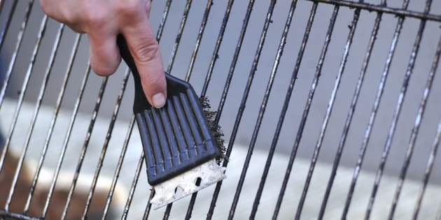 A person cleans a grill with a wire-bristle brush. The Standards Council of Canada released a request for proposals Wednesday to establish new national safety standards around barbecue brushes.