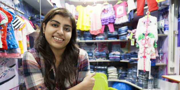 Young Indian woman selling clothes at a small store in a shopping mall in Delhi, India.