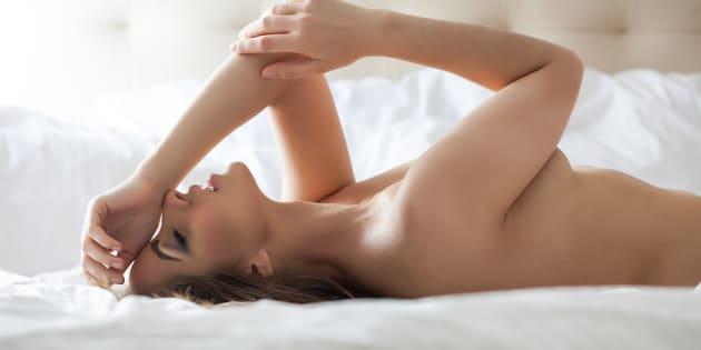 Una mujer tumbada en una cama y tal vez teniendo un orgasmo.