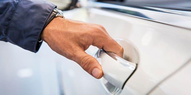 Man's hand on white car door handle