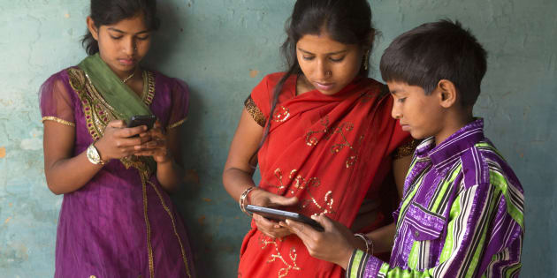 Indian brother and sisters using smartphone and tablet device.