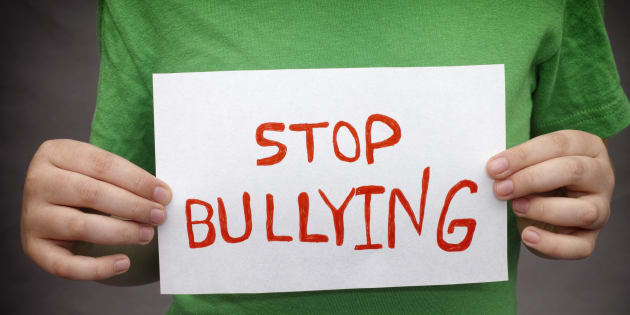 A young boy holds Stop bullying sign.
